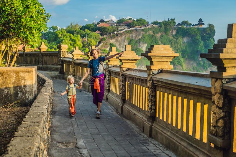 Viajantes do paizinho e do filho no templo de Pura Luhur Uluwatu, Bali, Indonésia Paisagem surpreendente - penhasco com céu azul  foto de stock royalty free