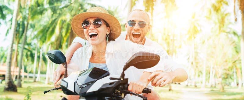 Viajantes felizes de sorriso dos pares que montam o velomotor durante suas f?rias tropicais sob palmeiras imagem de stock