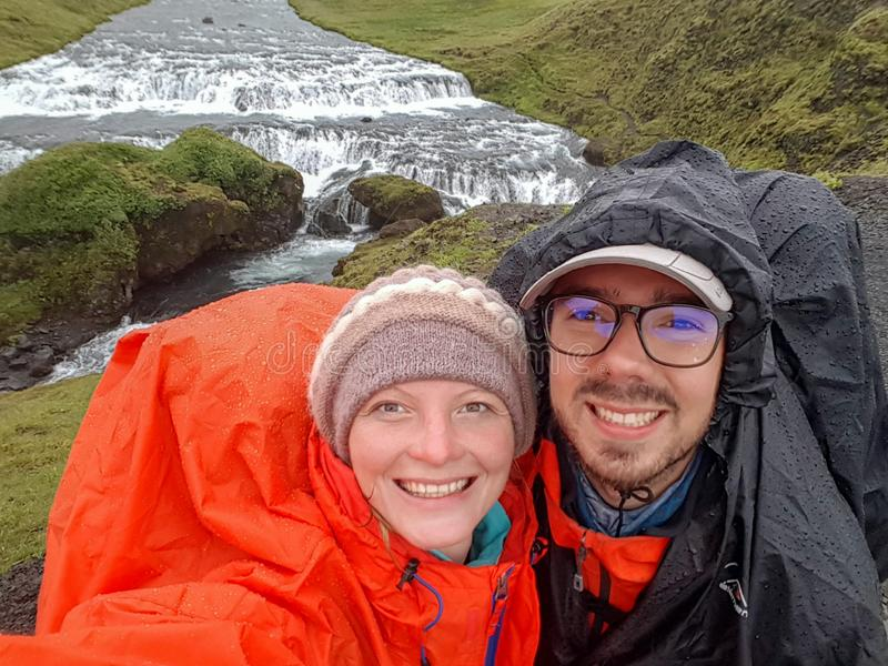 Viajantes felizes homem e mulher da aventura dos pares nas capas de chuva com cachoeira atrás Viagem da liberdade e conceito ativ fotografia de stock