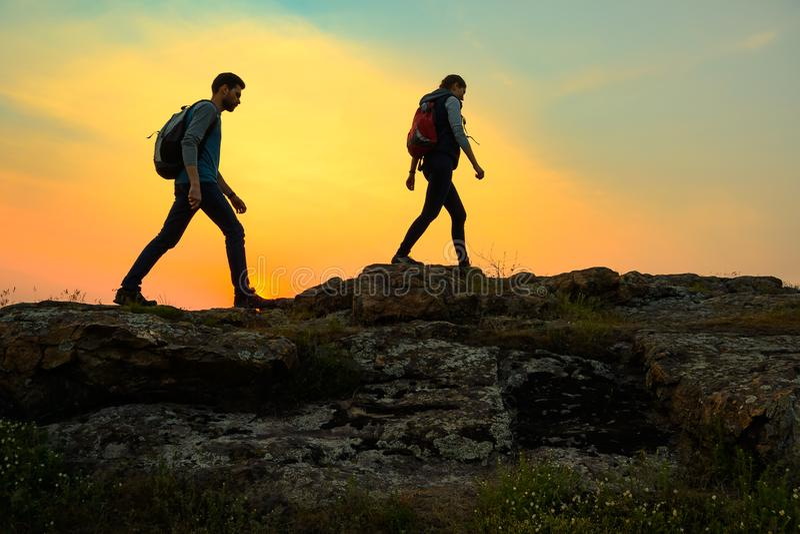 Viajantes felizes novos que caminham com as trouxas em Rocky Trail no por do sol do ver?o Conceito do curso e da aventura da fam? imagem de stock