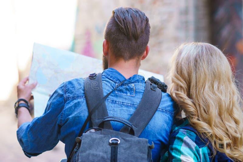 Viajantes novos com um mapa do turista Homem e mulher que têm férias Conceito dos mochileiros, da viagem e do turismo fotos de stock royalty free