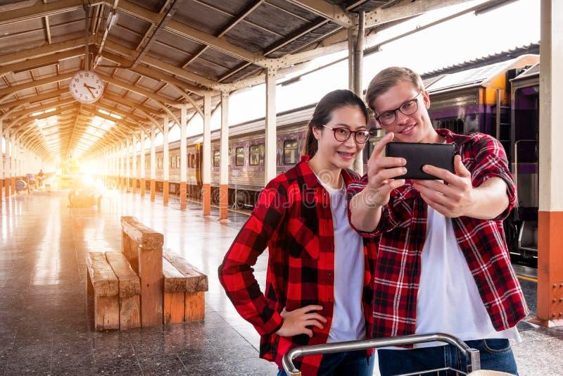 Viajantes novos felizesdo couplejunto nas férias que tomam um selfie no telefone no estação de caminhos de ferro, conceito do  imagem de stock