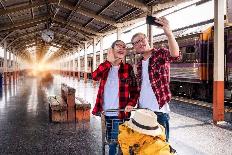 Viajantes novos felizesdo couplejunto nas férias que tomam um selfie no telefone no estação de caminhos de ferro, conceito do  fotografia de stock