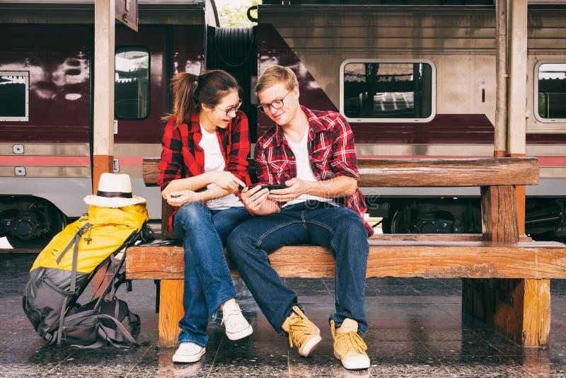 Viajantes novos felizesdo couplejunto no telefone do uso das férias em imagem de stock