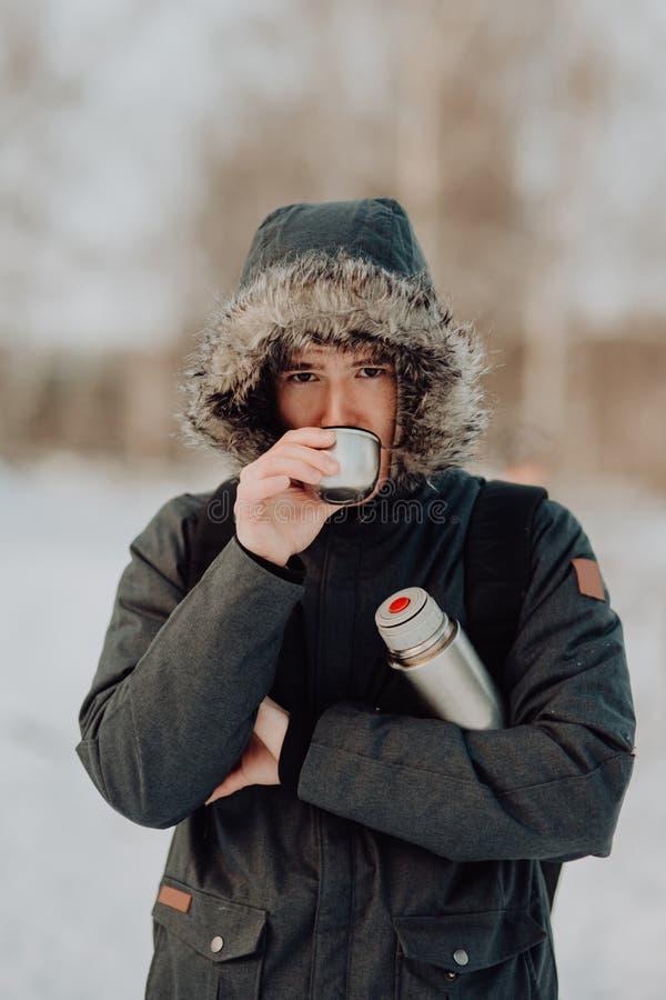 Viajantes que bebem o chá na caneca da garrafa térmica nas montanhas com neve fotos de stock