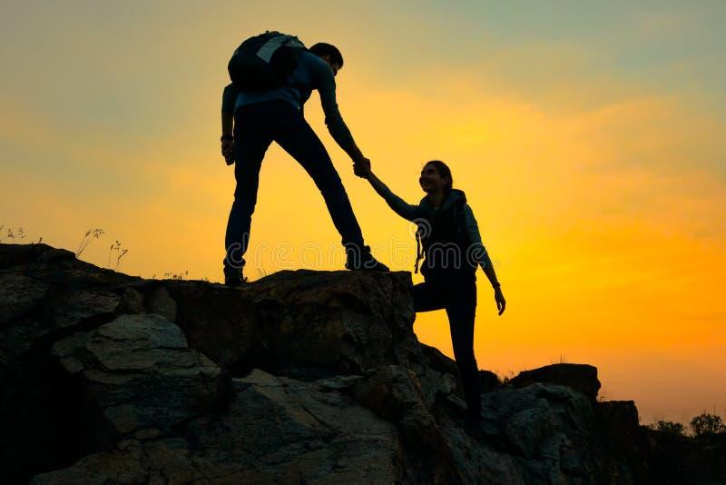 Viajantes que caminham nas montanhas no por do sol Mulher de ajuda do homem a escalar à parte superior Curso e aventura da fam?li fotografia de stock