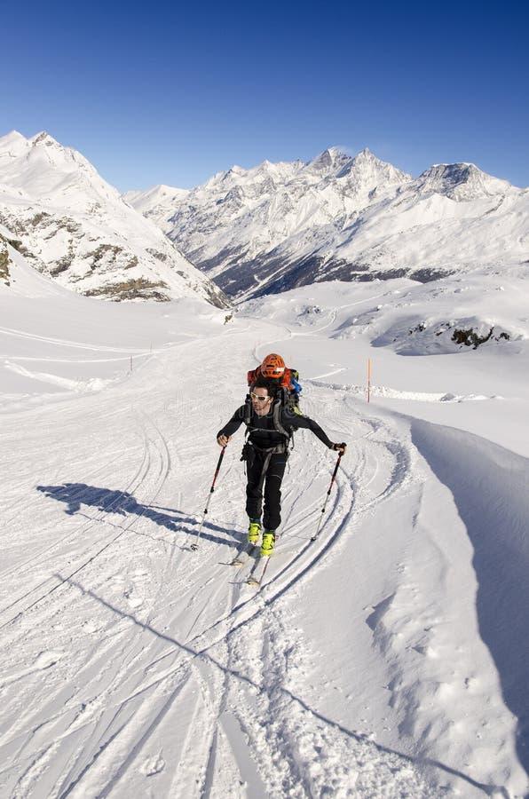 Viajar al esquiador en las montañas suizas fotografía de archivo