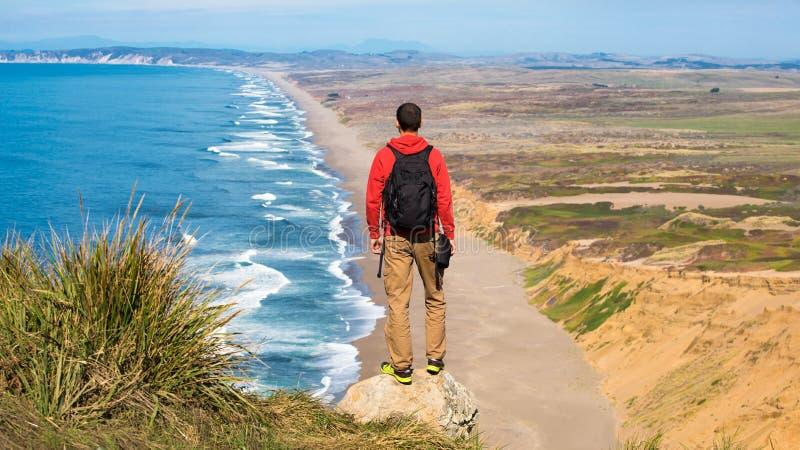 Viajar em Point Reyes National Seashore, homem Hiker com mochila deslumbrando, Califórnia, EUA imagens de stock royalty free