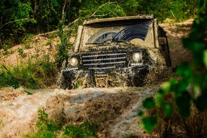 Viaje campo a trav?s en el camino de la monta?a El fango y el agua salpican en de competir con de camino Indique los neum?ticos d imágenes de archivo libres de regalías