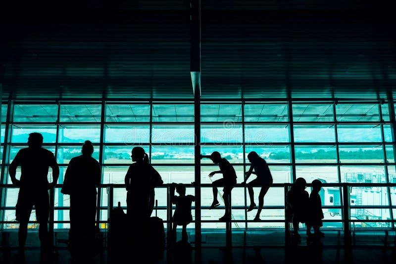 Viaje con concepto de los ni?os Silueta de los pasajeros grandes de una familia que esperan el embarque en aeropuerto terminal imágenes de archivo libres de regalías