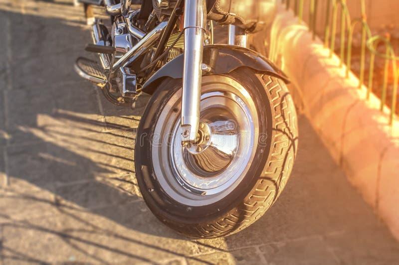 Viaje de automóvel a primeira roda da bicicleta estacionada na rua da cidade com sol ardente imagem de stock royalty free