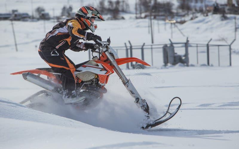 Viaje de la moto de nieve del snowbike de Enduro con la bici de la suciedad alta en las montañas imagenes de archivo