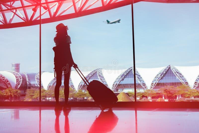 Viaje de la mujer de la silueta con el equipaje que mira sin la ventana el aeropuerto fotografía de archivo libre de regalías
