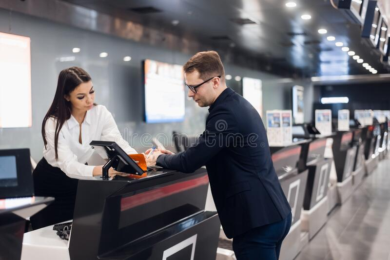 Viaje de negocios Un hombre de negocios joven y guapo de traje que lleva su pasaporte y habla con una mujer en el mostrador de fa fotos de archivo libres de regalías