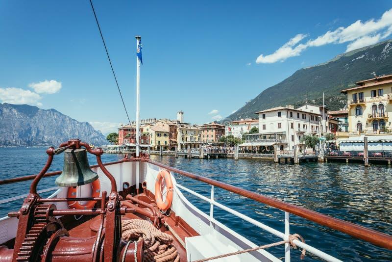 Viaje del barco: Arco del barco con la campana del barco, visi?n sobre el agua azul azul, cordillera y peque?o pueblo Lago di Gar imagen de archivo