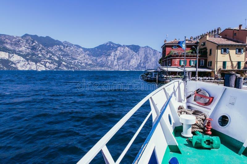 Viaje del barco: Arco del barco, visi?n sobre el agua azul azul, pueblo y cordillera Lago di Garda, Italia imagen de archivo