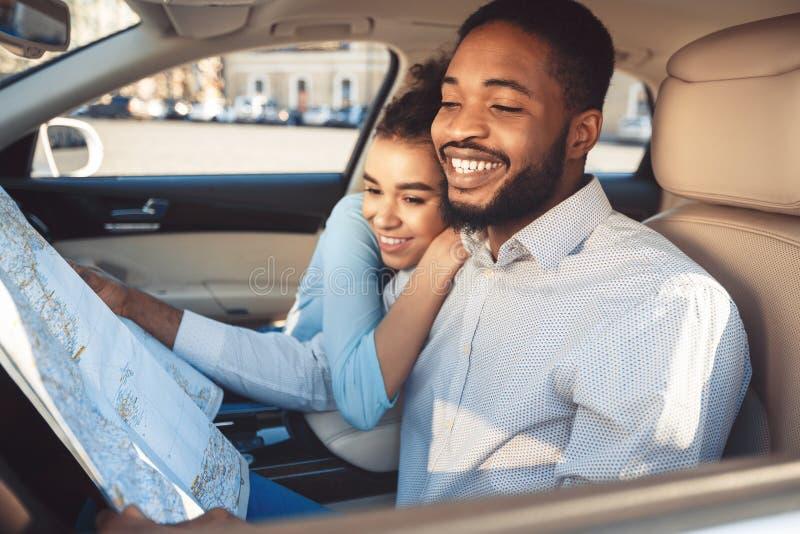 Viaje del coche. Feliz pareja afro con mapa en auto imagen de archivo