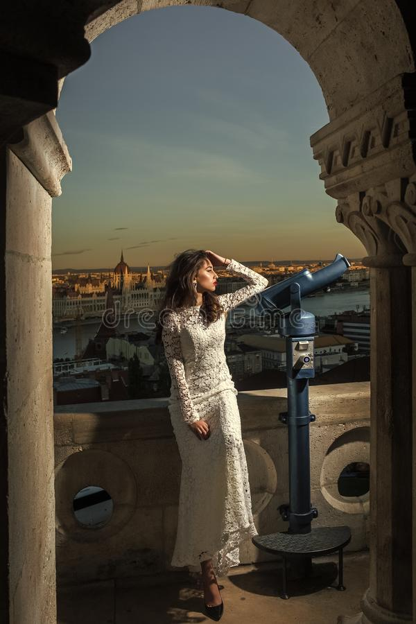 Viaje del modelo de moda el vacaciones Mujer con el telescopio en el punto de vista en paisaje urbano Mujer sensual con el pelo l fotos de archivo