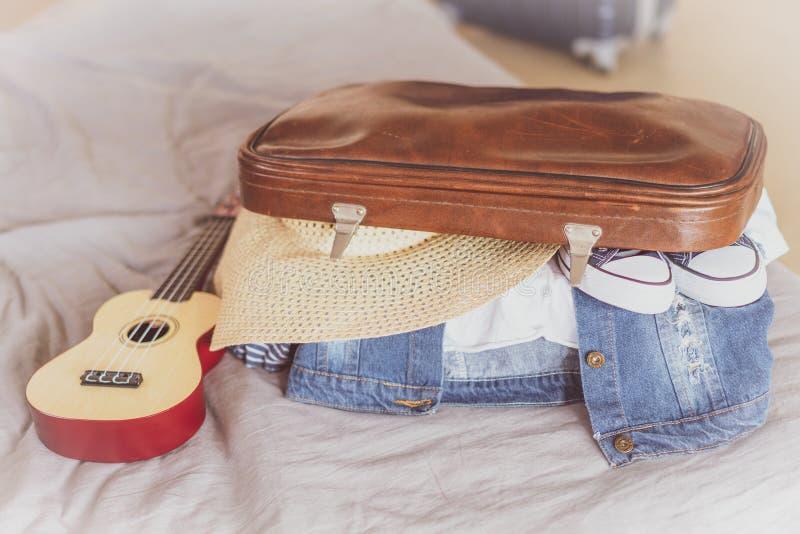 Viaje del verano y concepto de las vacaciones, maleta del embalaje de la mujer joven en casa imagen de archivo