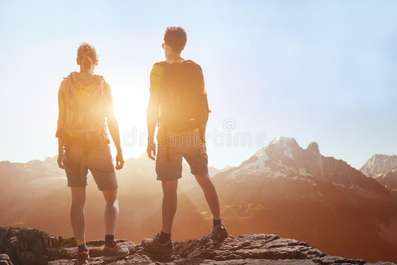 Viaje, el viajar de la gente, caminando en montañas, pares de los caminantes que miran paisaje panorámico