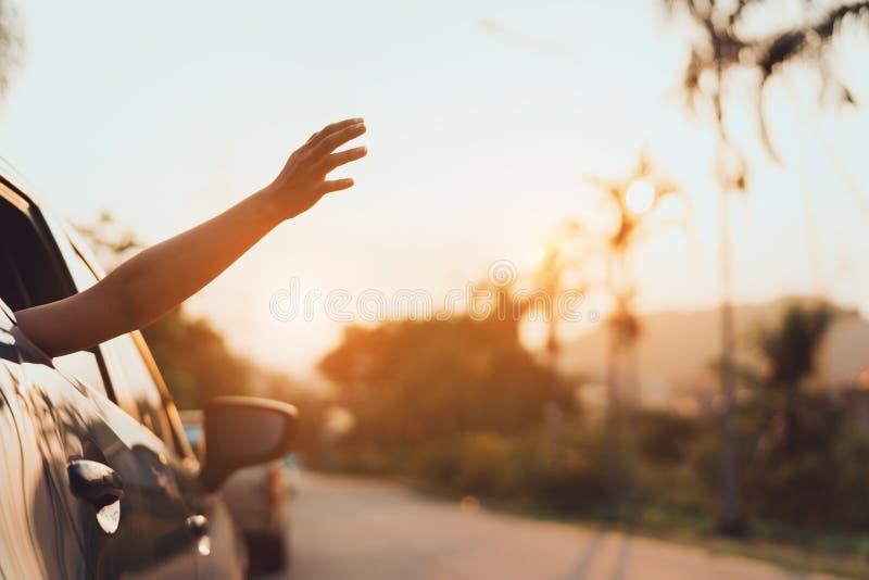 Viaje en coche de la ventana trasera que conduce el viaje por carretera de las vacaciones de verano de la mujer en coche azul imagenes de archivo