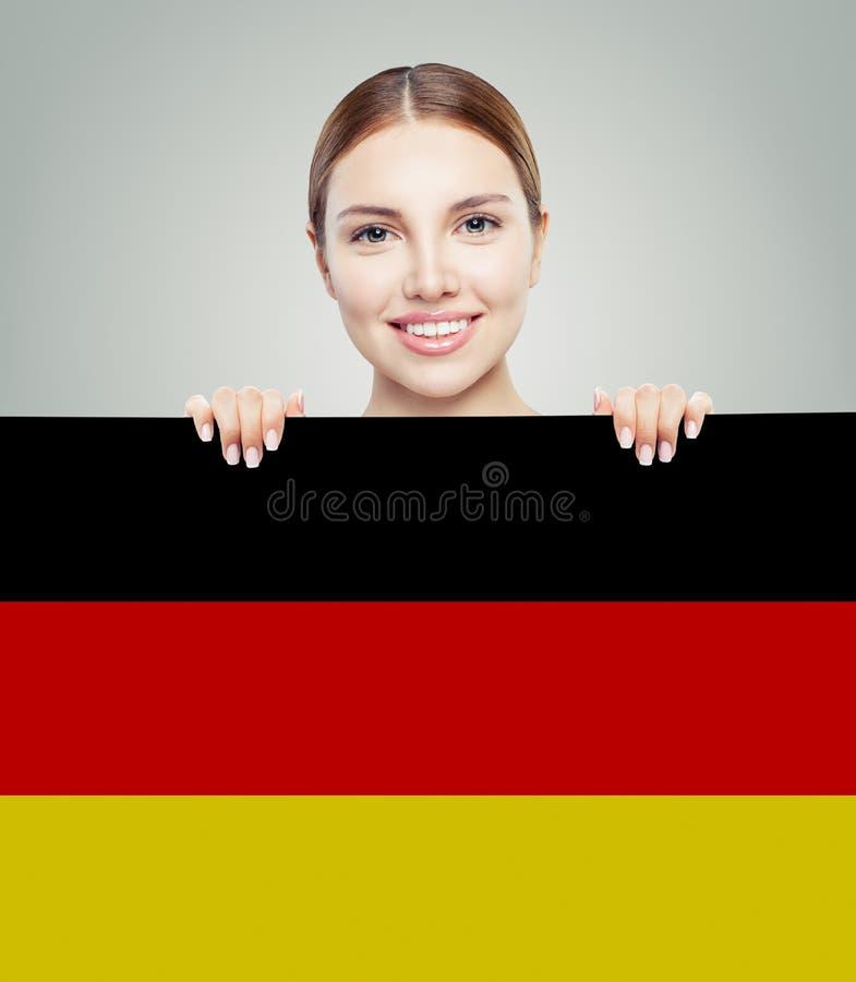Viaje en el concepto de Alemania Mujer bonita que muestra el fondo de la bandera de Alemania imágenes de archivo libres de regalías