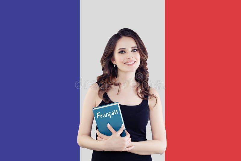 Viaje en Francia y aprender lengua francesa Estudiante de mujer hermoso con el libro contra el retrato francés de la bandera imagen de archivo
