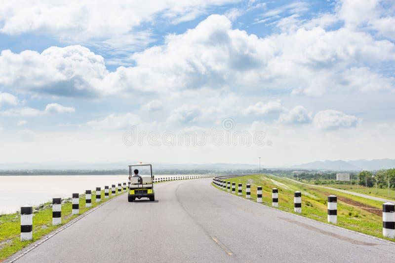 Viaje escénico del camino del paisaje en la carretera vacía y el carro de golf eléctrico imagenes de archivo