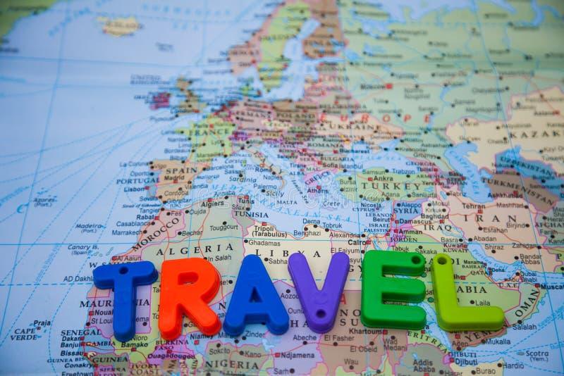 Viaje escrito con los bloques del juguete en un mapa del mundo imagen de archivo