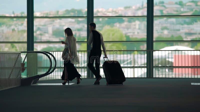 Viaje, hombre y mujer de negocios caminando a la escalera móvil en el aeropuerto, equipaje que lleva imágenes de archivo libres de regalías