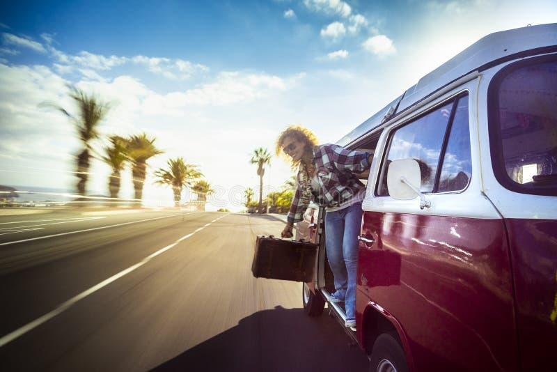 Viaje rubio feliz sonriente de la mujer en una furgoneta vieja roja rápidamente en el camino que mira la calle de la puerta abier fotografía de archivo libre de regalías