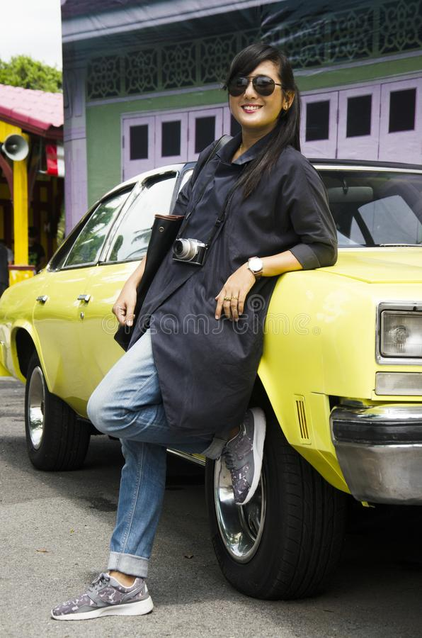 Viaje tailandés asiático de la mujer y presentación con el coche clásico amarillo retro fotos de archivo