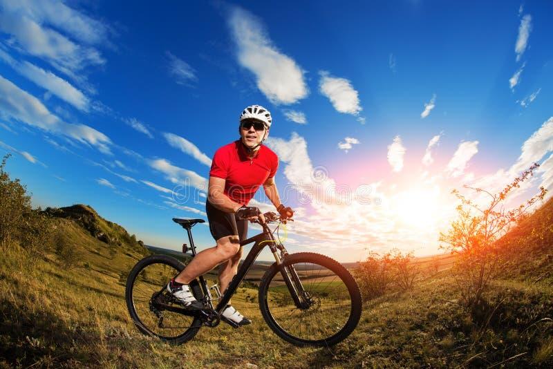 Viaje turístico del motorista en la bici de montaña Autumn Landscape Deportista en la bicicleta en jersey rojo y el casco blanco foto de archivo libre de regalías