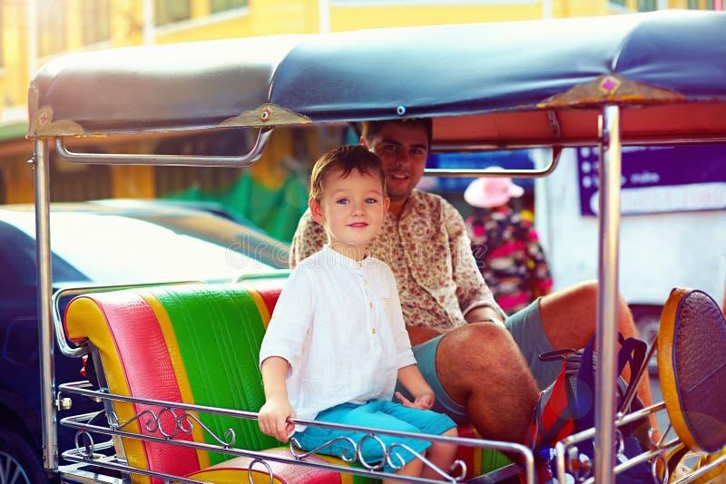 Viaje turístico feliz de la familia a través de la ciudad asiática en el taxi del tuk-tuk fotos de archivo
