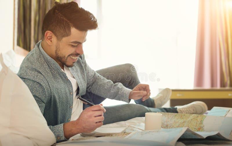 Viajero árabe joven del hombre que miente en cama y que estudia el mapa fotos de archivo