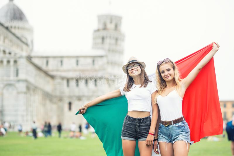 Viajero adolescente joven de las muchachas con la bandera italiana antes de la torre histórica en la ciudad Pisa - Italia fotos de archivo
