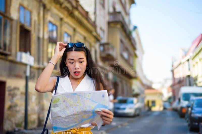 Viajero asiático con las calles de exploración de una ciudad del mapa fotografía de archivo
