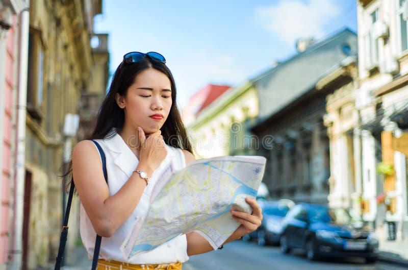 Viajero asiático con un mapa que explora las calles de la ciudad fotografía de archivo