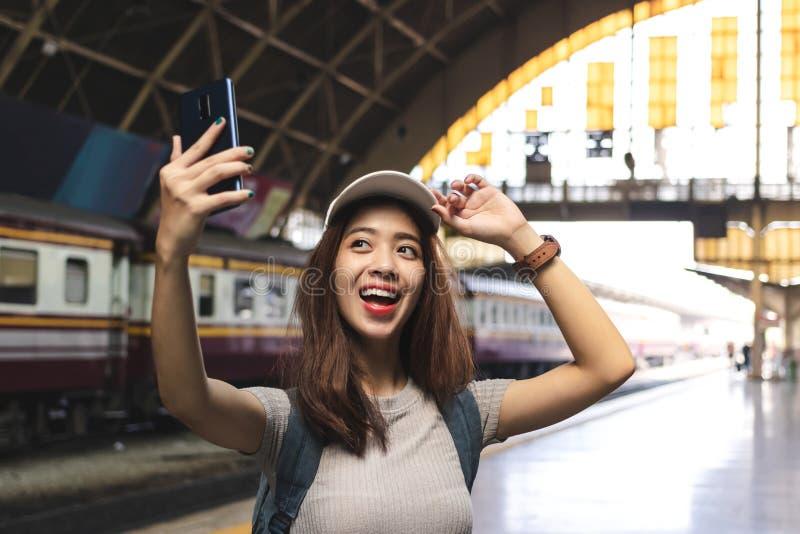 Viajero asi?tico joven alegre de la mujer con la mochila que toma una foto o un selfie en la estaci?n de tren Concepto de la form fotos de archivo libres de regalías