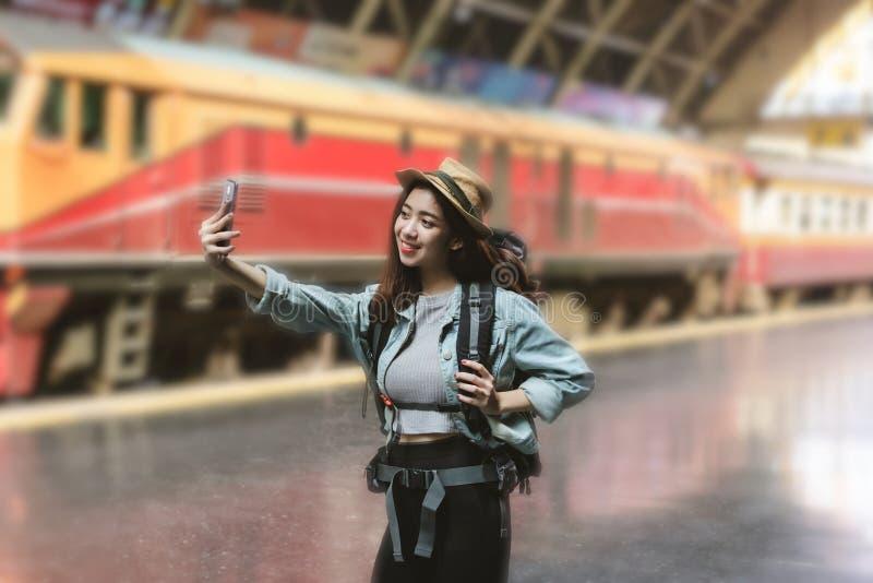 Viajero asi?tico joven alegre de la mujer con la mochila que toma una foto o un selfie en la estaci?n de tren Concepto de la form foto de archivo