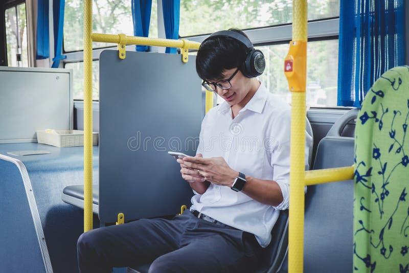 Viajero asi?tico joven del hombre que se sienta en un autob?s que escucha la m?sica en smartphone mientras que sonrisa de feliz,  fotografía de archivo libre de regalías