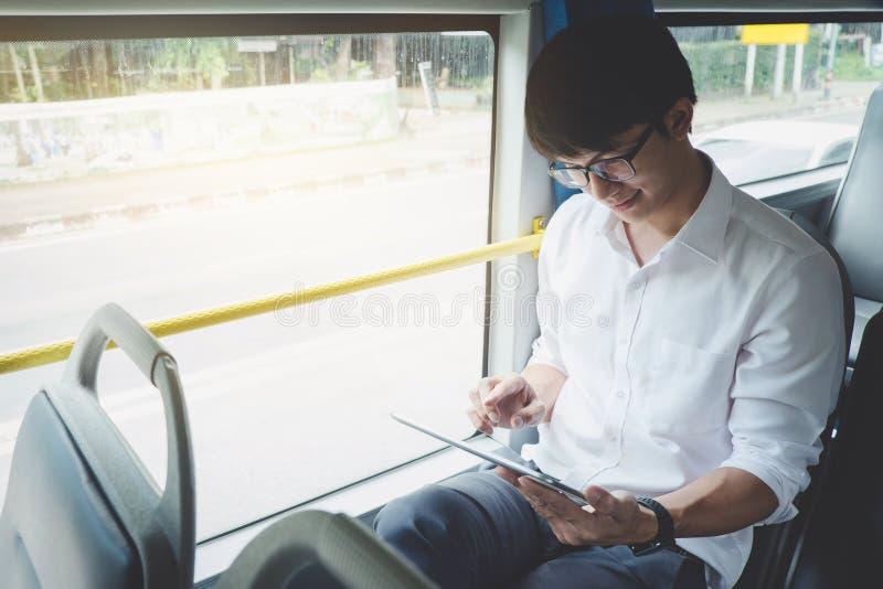 Viajero asi?tico joven del hombre que se sienta en un autob?s usando el v?deo del reloj de la tableta o que juega al juego mientr imagen de archivo