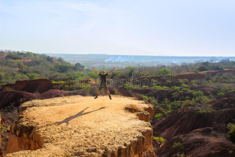 Viajero caucásico caucásico en la ropa de deportes que salta de la felicidad de la libertad en una roca en el fondo de la natural foto de archivo
