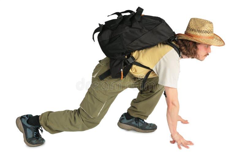 Viajero con el morral en sombrero de paja en todos los fours foto de archivo