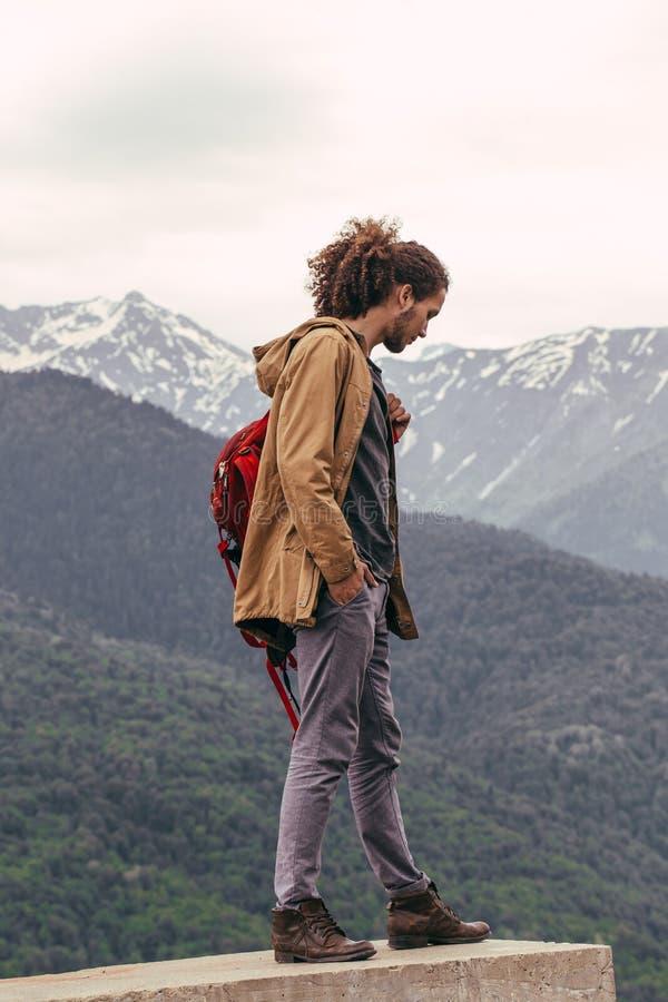 Viajero con la mochila roja que camina en la montaña Concepto de la libertad de las vacaciones de la aventura de la forma de vida imagenes de archivo