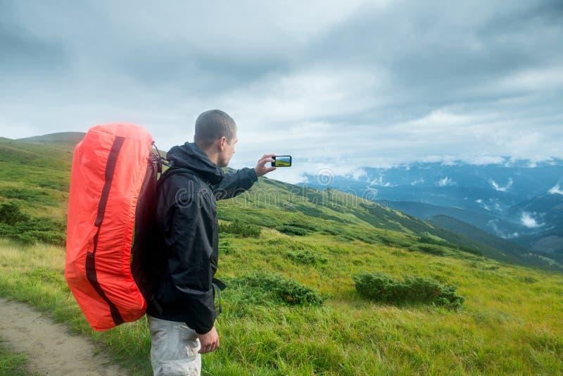 Viajero con la mochila y smartphone en las montañas fotografía de archivo libre de regalías