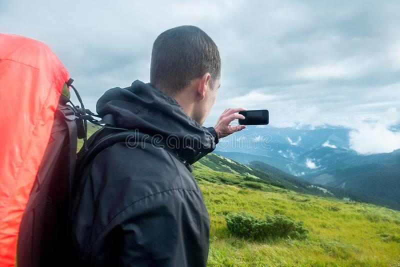 Viajero con la mochila y smartphone en las montañas foto de archivo libre de regalías