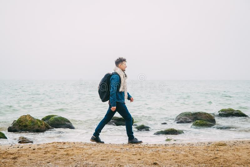 Viajero con una situación de la mochila cerca de una roca contra un mar hermoso con las ondas, muchacho elegante del inconformist fotografía de archivo