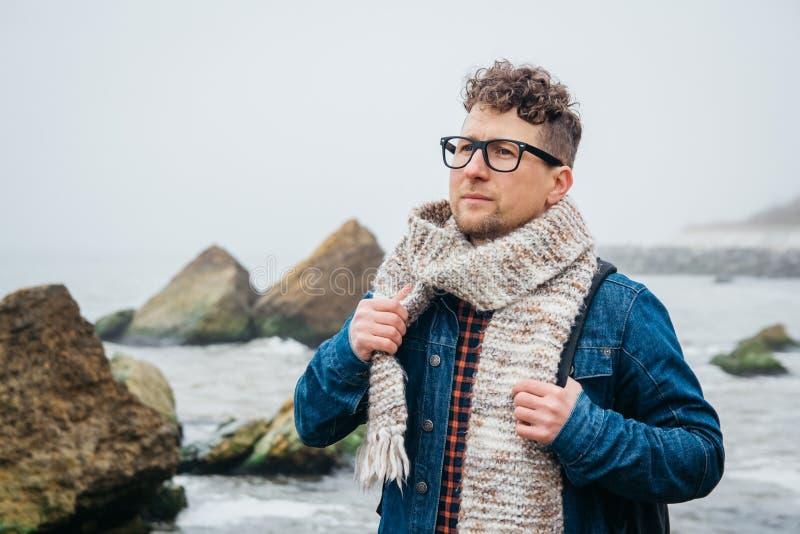 Viajero con una situaci?n de la mochila en una roca contra un mar hermoso con las ondas, muchacho elegante del hombre del inconfo fotografía de archivo