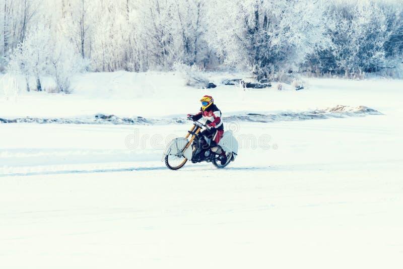 Viajero de la motocicleta en la trayectoria del camino de la estepa del invierno de la nieve imagen de archivo